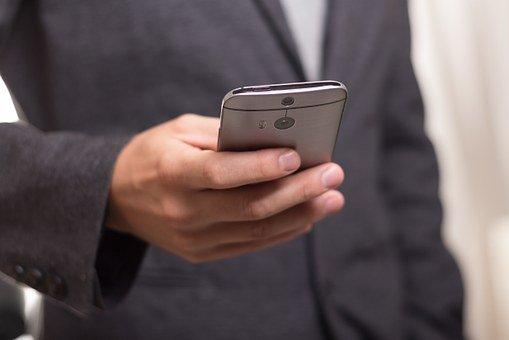 mobil drží muž v saku